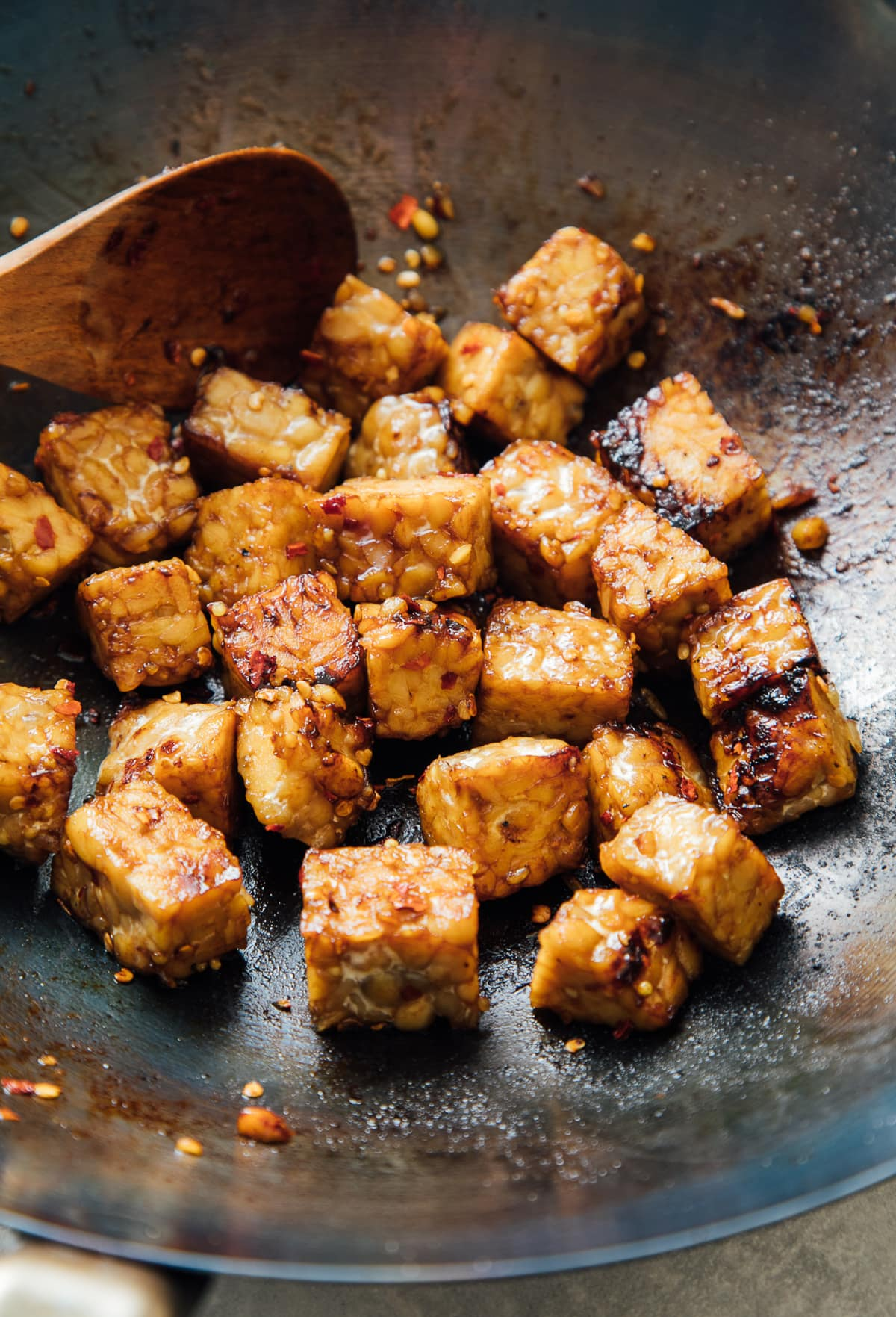 side angle view of stir fried tempeh in a wok.