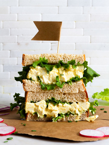 vegan egg salad sandwich with leafy greens sliced in half and stacked.