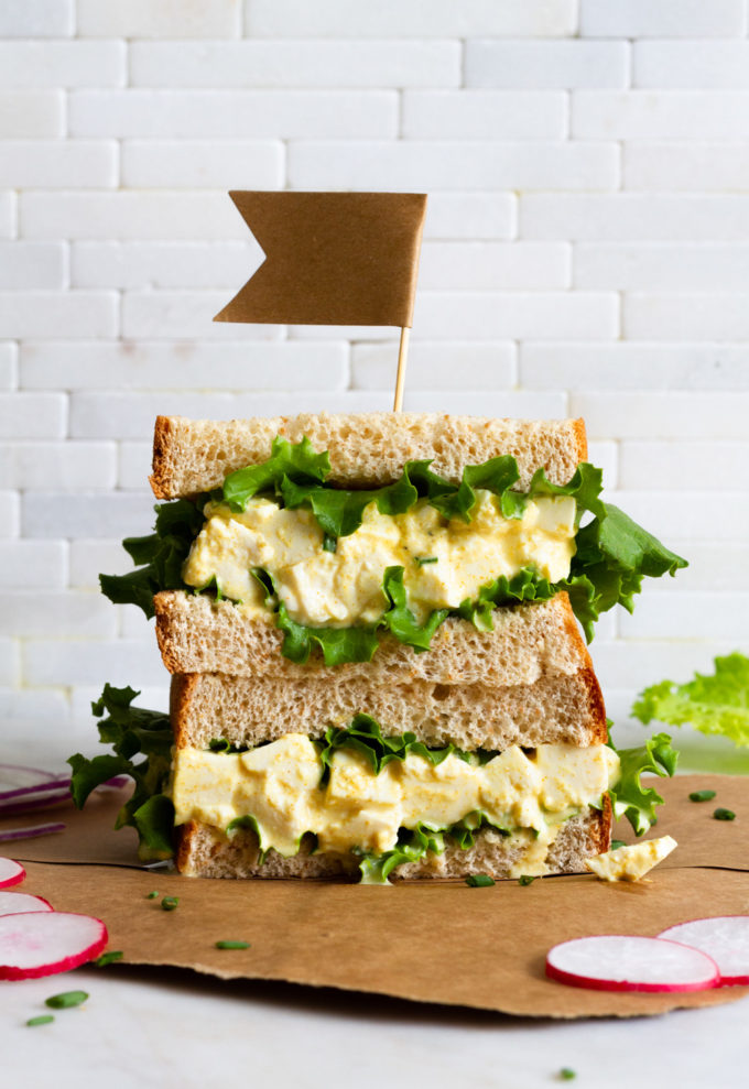 vegan egg salad sandwich with leafy greens sliced in half and stacked