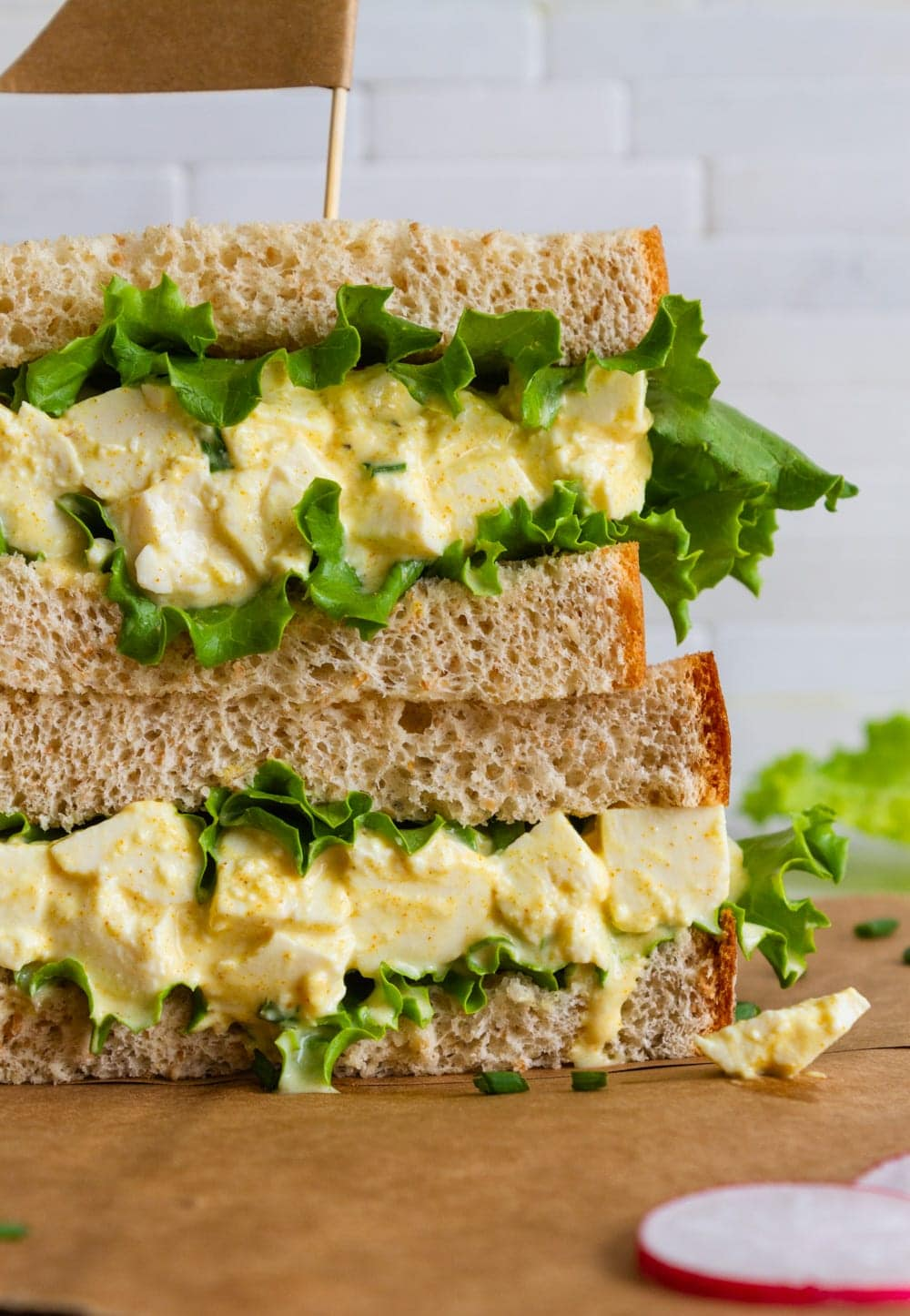 head on view of vegan egg salad sandwich with leafy greens sliced in half and stacked.