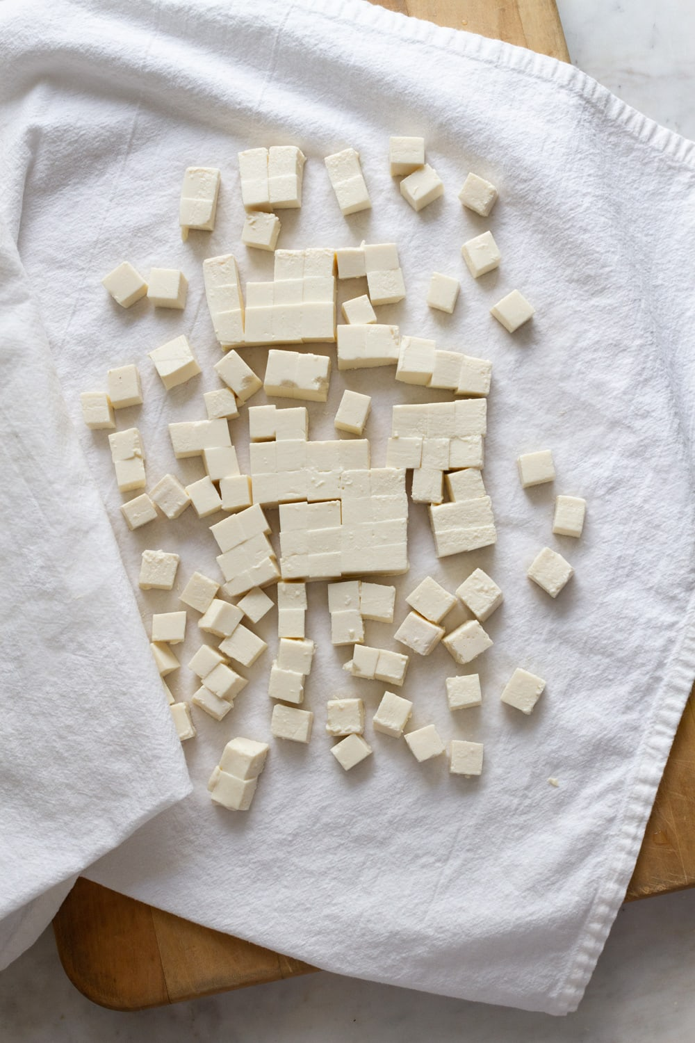 top down view of cubed tofu in between a dish towel to remove excess water.