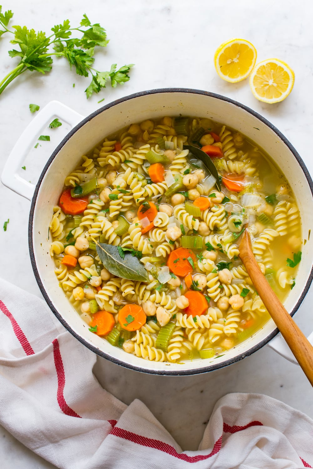 top down view of a big pot of homemade vegan chickpea noodle soup with wooden spoon.