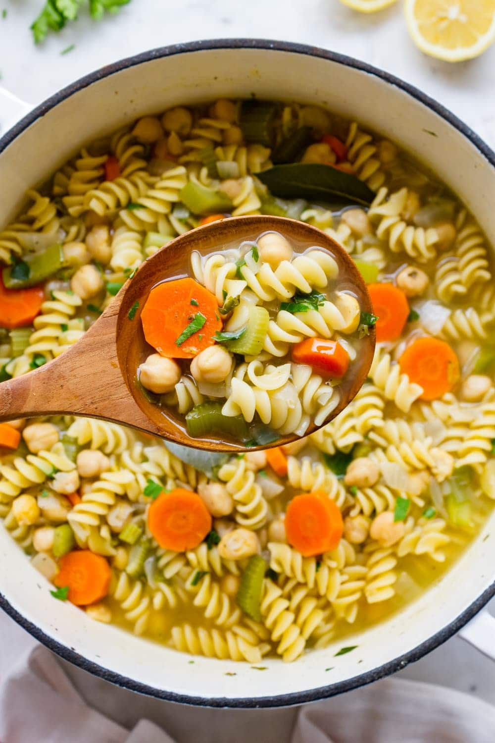 top down view of a wooden spoon filled with hearty vegan chickpea noodle soup.