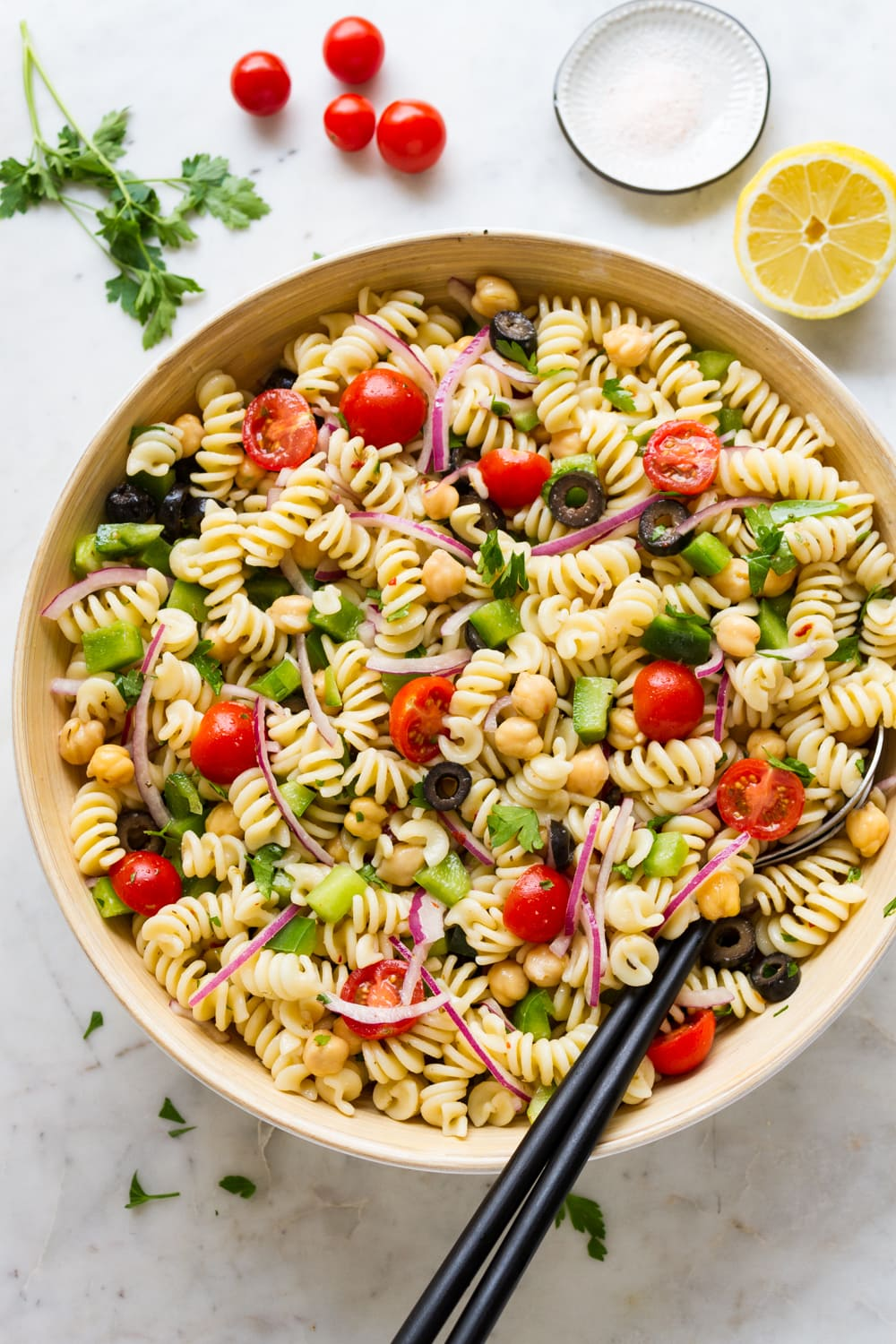 top down view of freshly mixed easy vegan pasta salad in a large serving bowl.