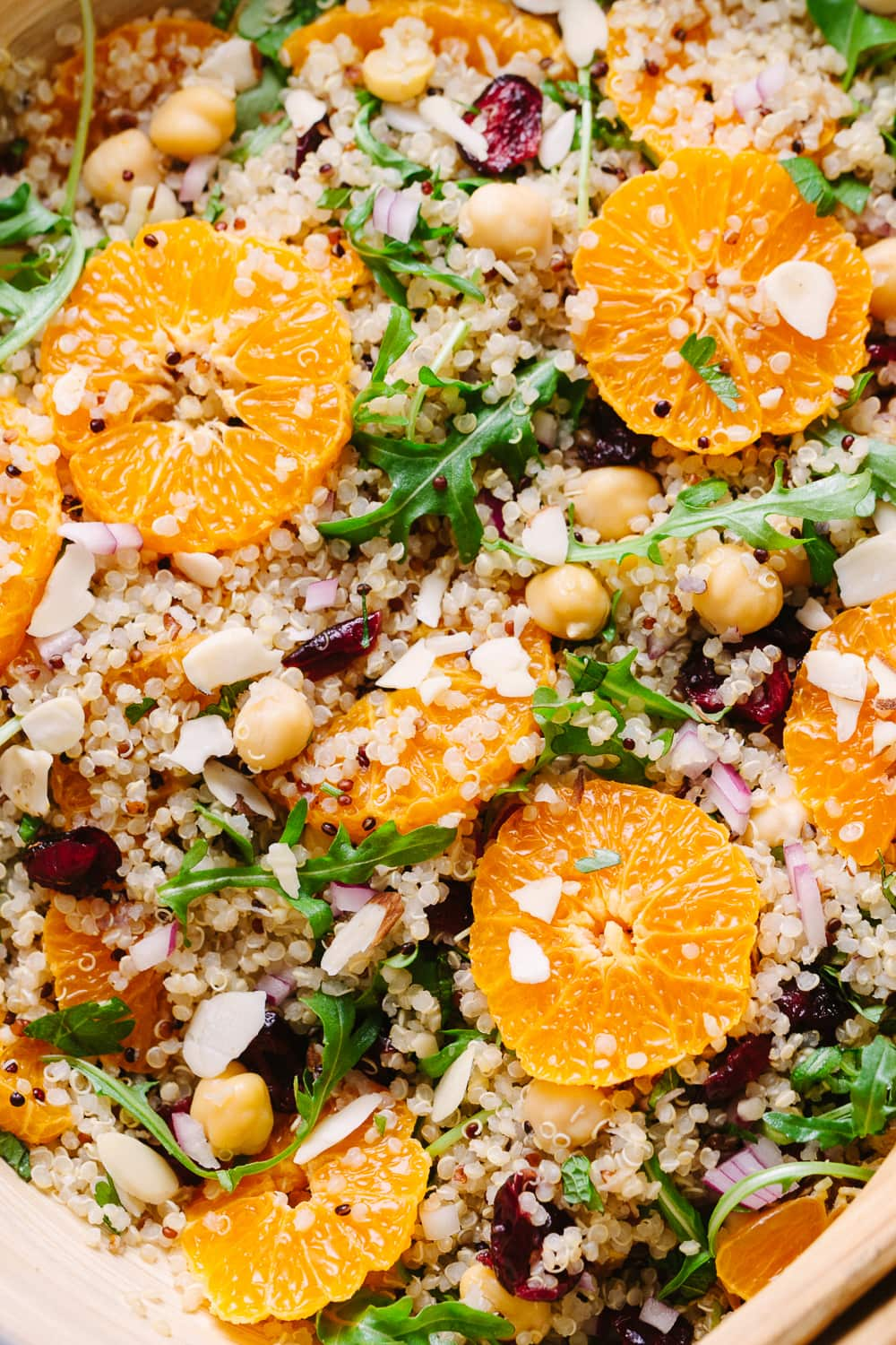 close up, top down view of quinoa salad with orange, cranberry and mint freshly tossed and ready to serve.