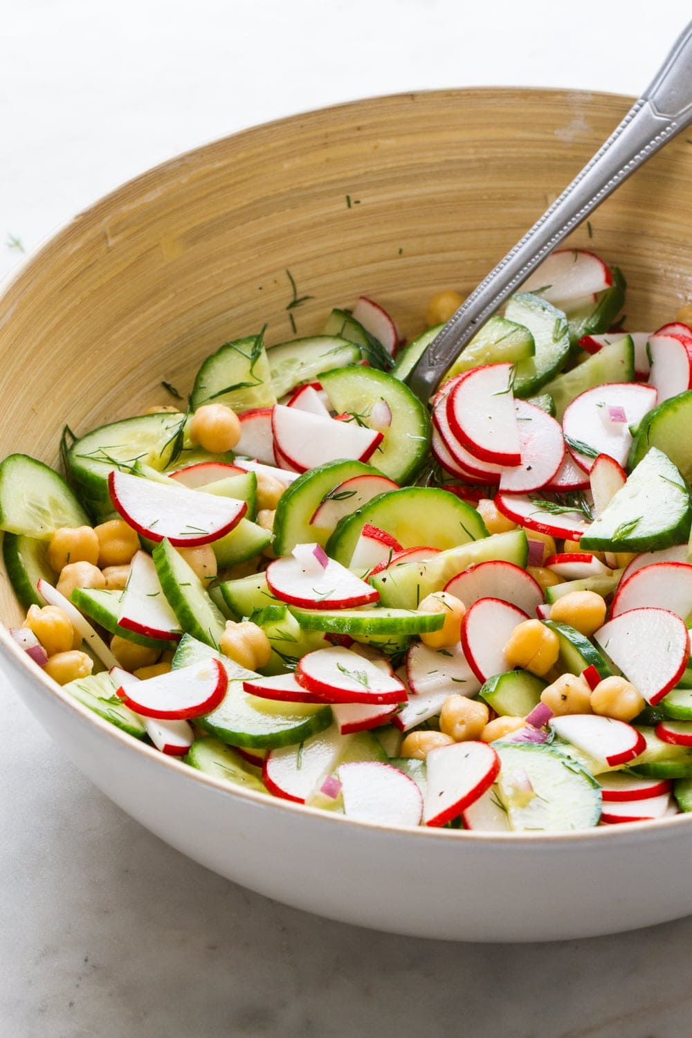 side angle top down view of a white bowl serving bowl filled with radish and cucumber salad with a serving spoon on a marble slab