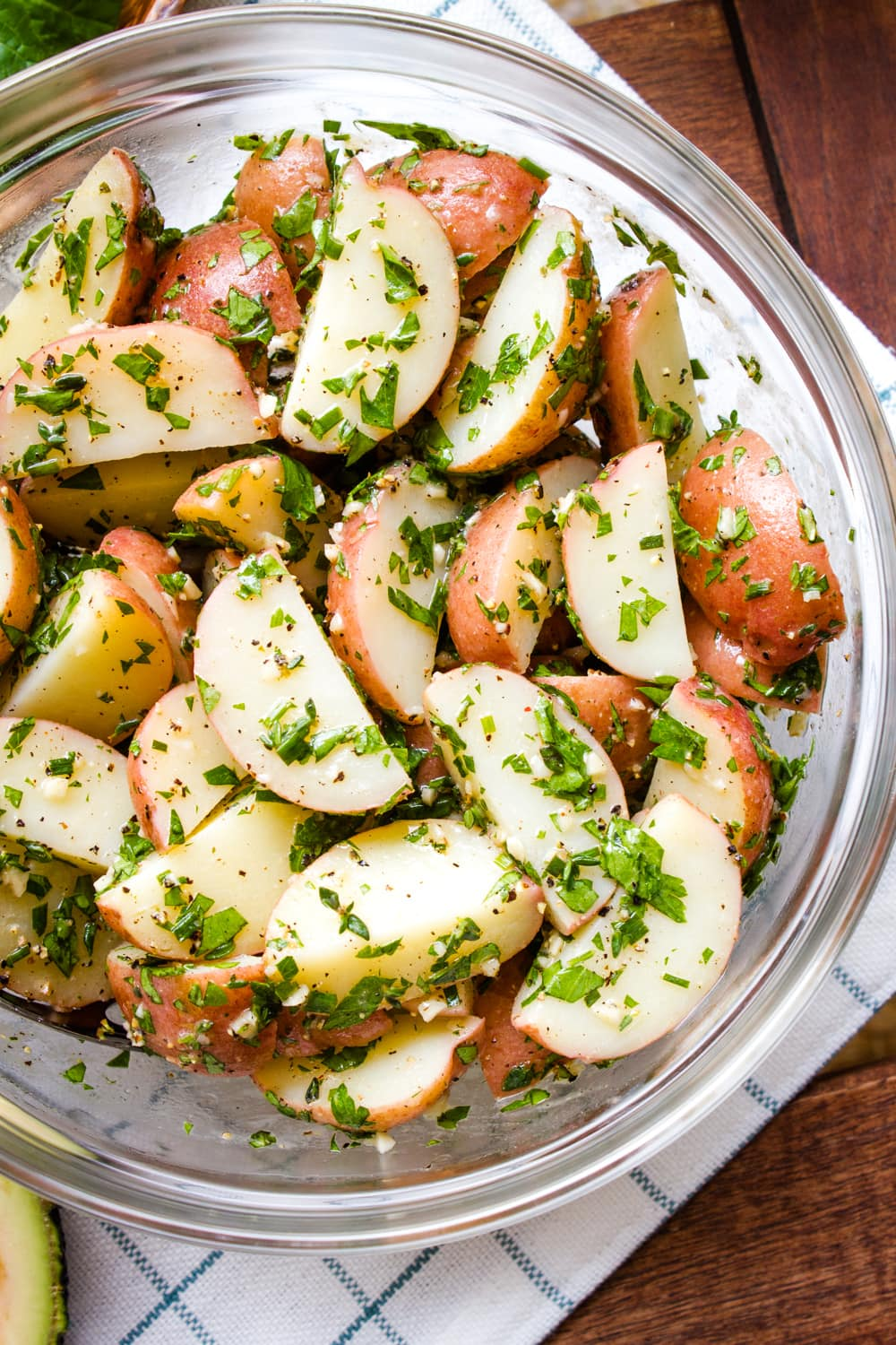 top down view of mayo free herbed potato salad in a glass bowl.