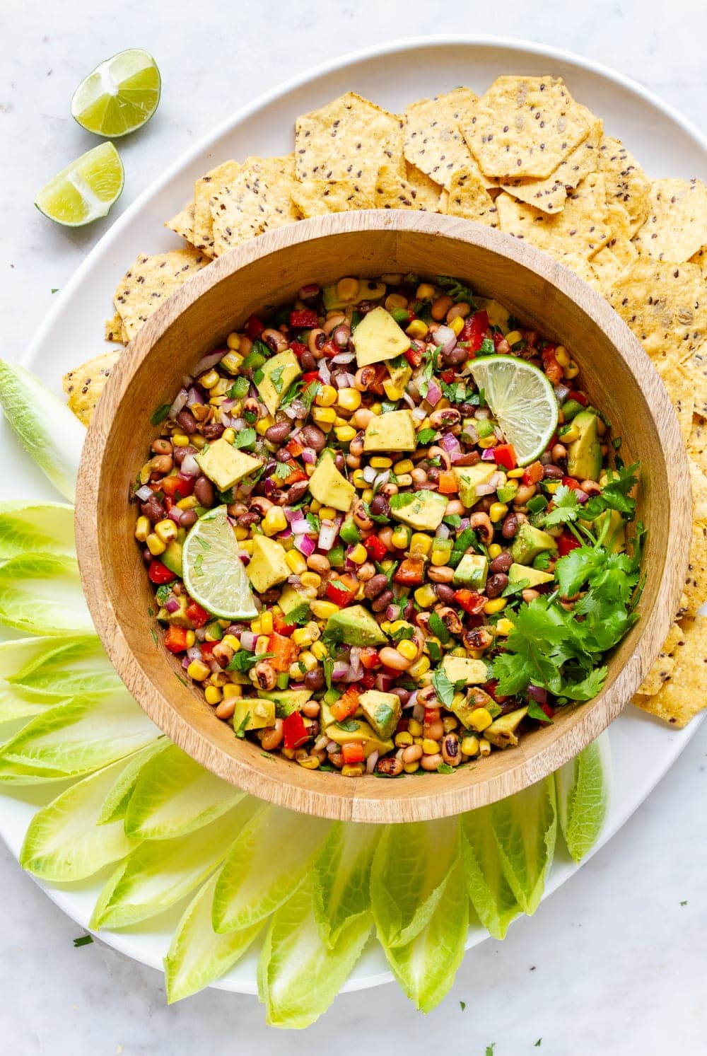 top down view of a platter with bowl full of Texas cowboy caviar surrounded by endive and tortilla chips for scooping.
