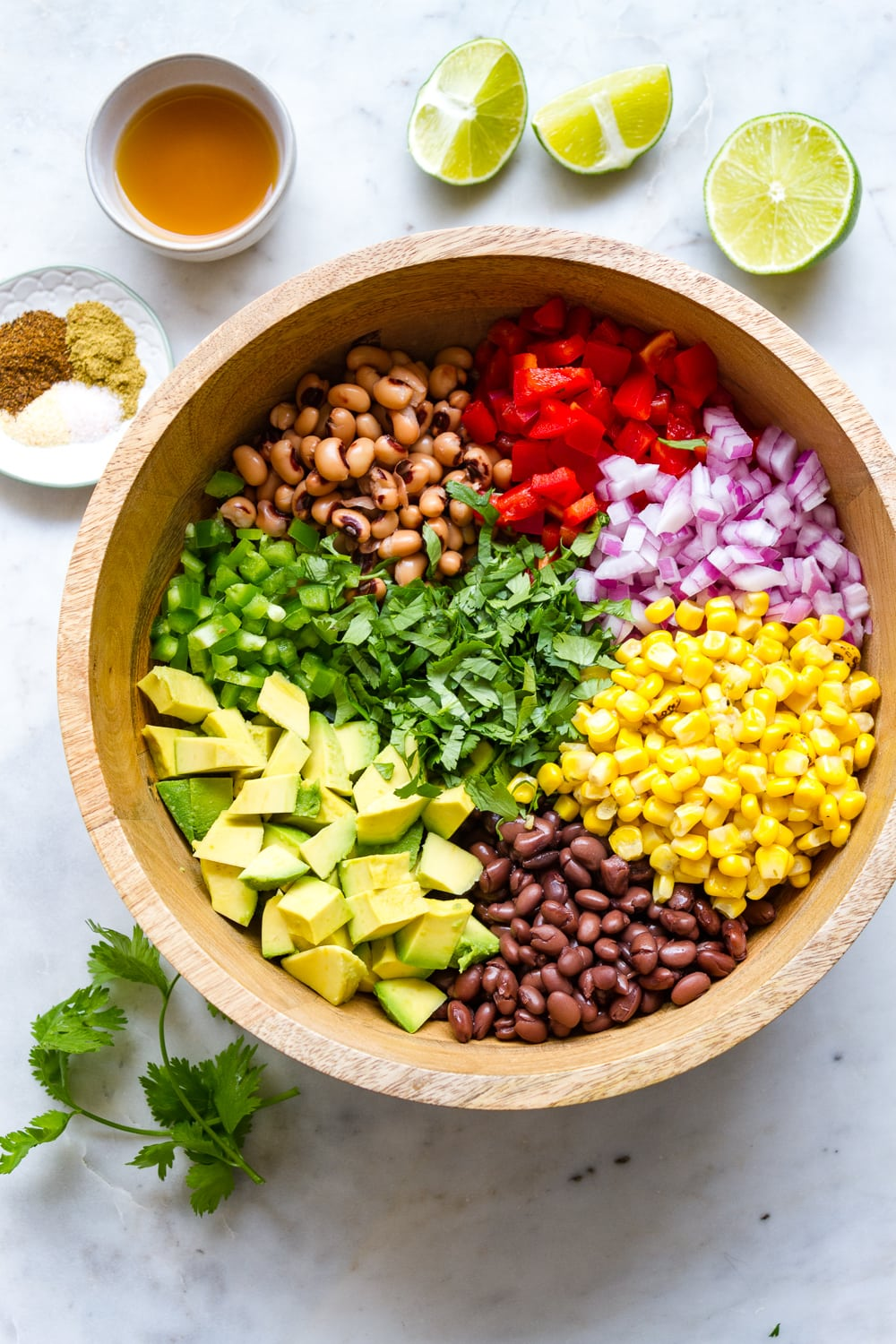 top down view of a wooden bowl with individual ingredients added for making Texas cowboy caviar (aka Texas caviar)