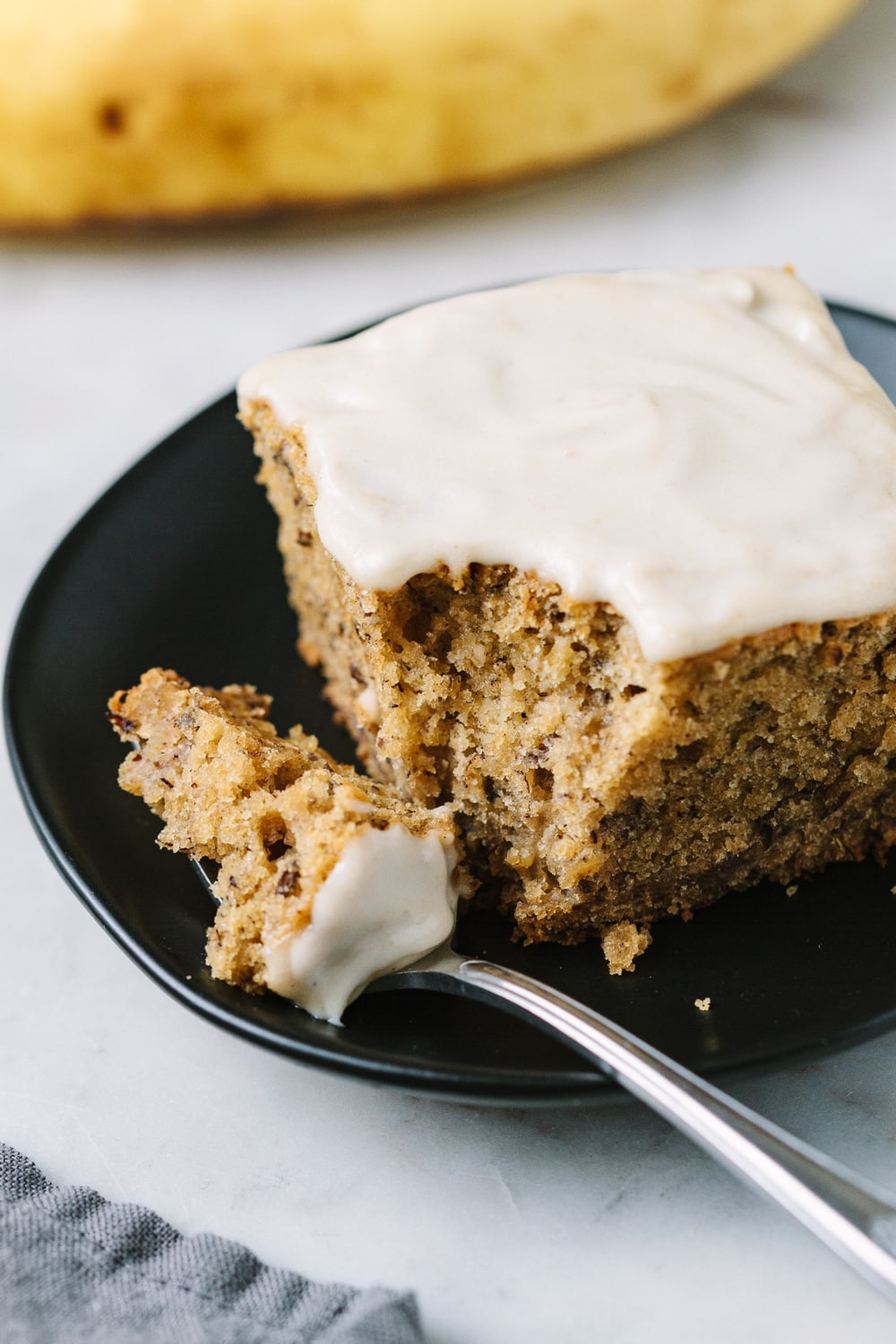 side angle view of a slice of banana cake with cashew frosting on a small black plate.