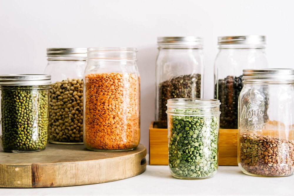 an assortment of legumes in mason jars.