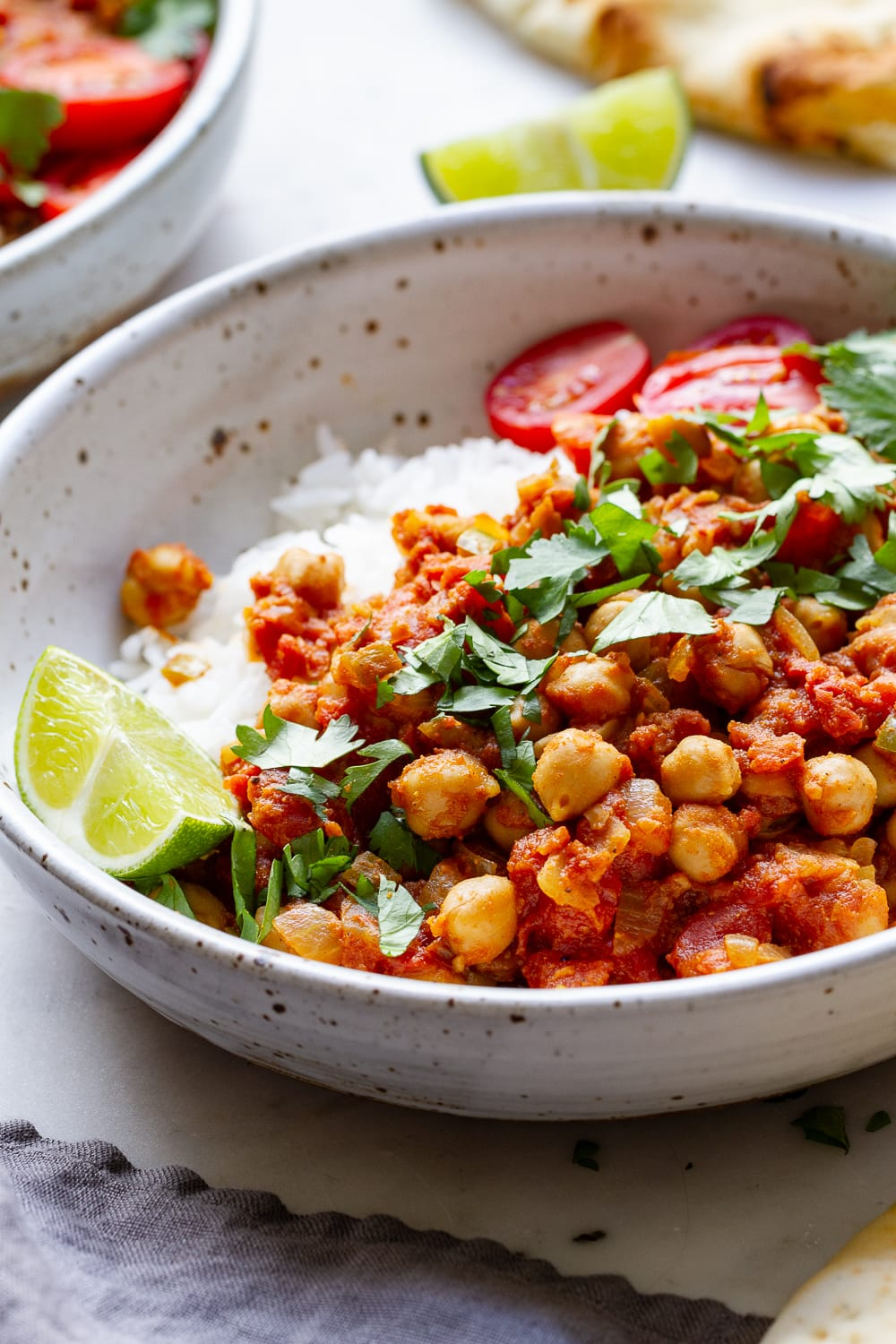 side angle view of easy chana masala in a bowl with rice, lime and cilantro.