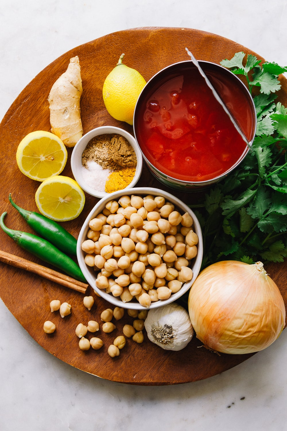 top down view of ingredients for easy chana masala recipe on a wooden charger.