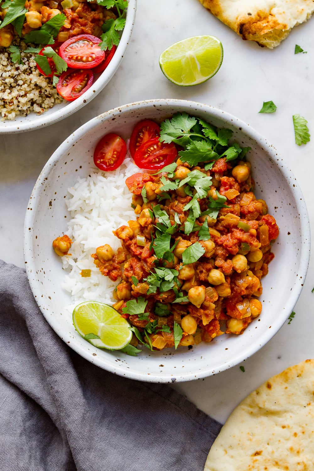 top down view of healthy chana masala in a bowl with rice, lime and cilantro.