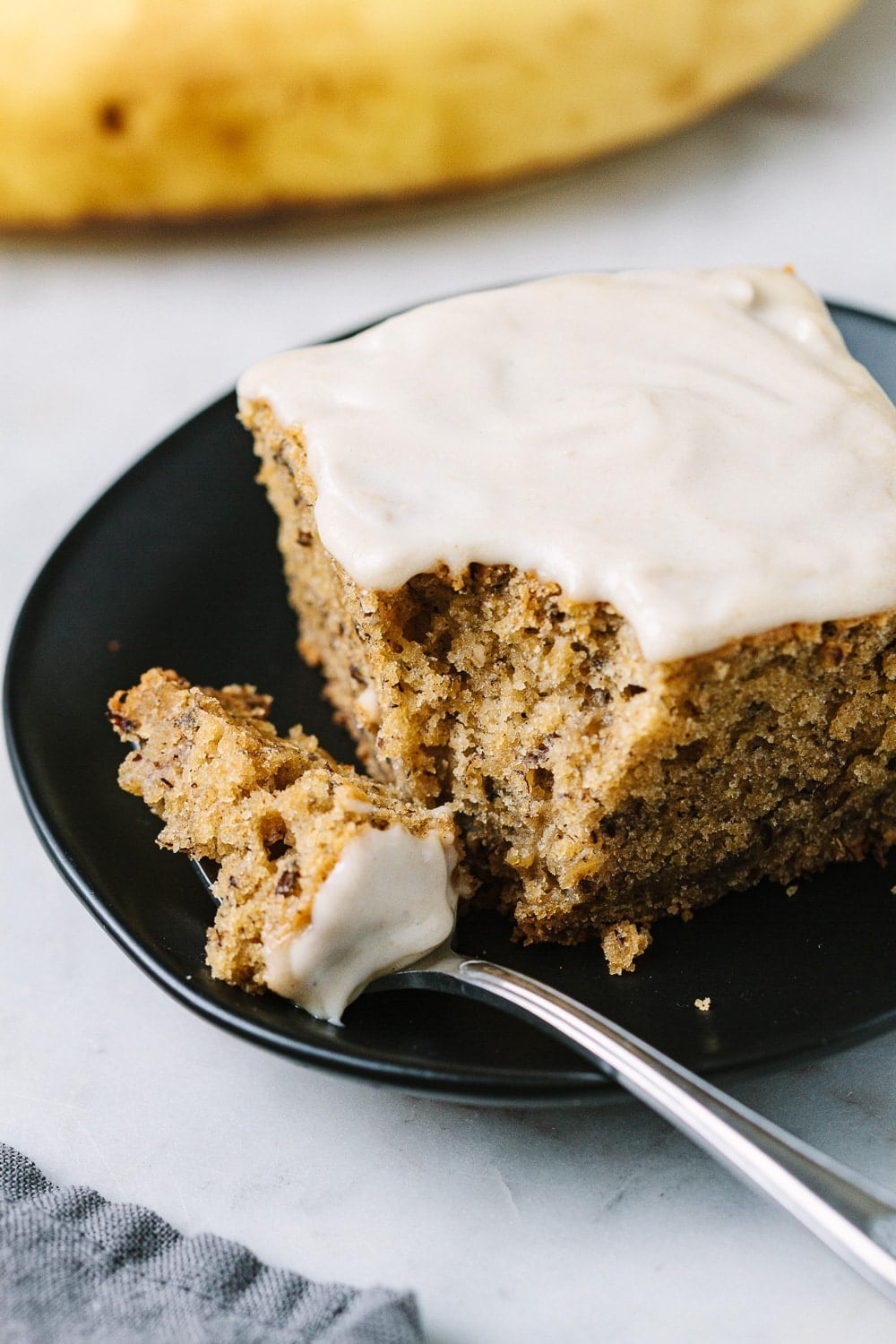 slice of vegan banana cake with a slice on a fork resting on a small black plate.