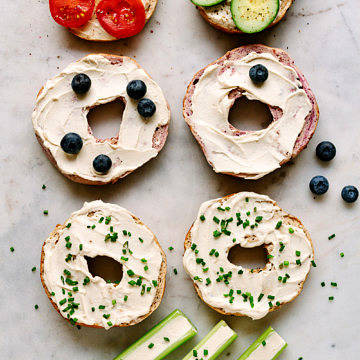 top view of an assortment of bagels topped with vegan cream cheese and various toppings.