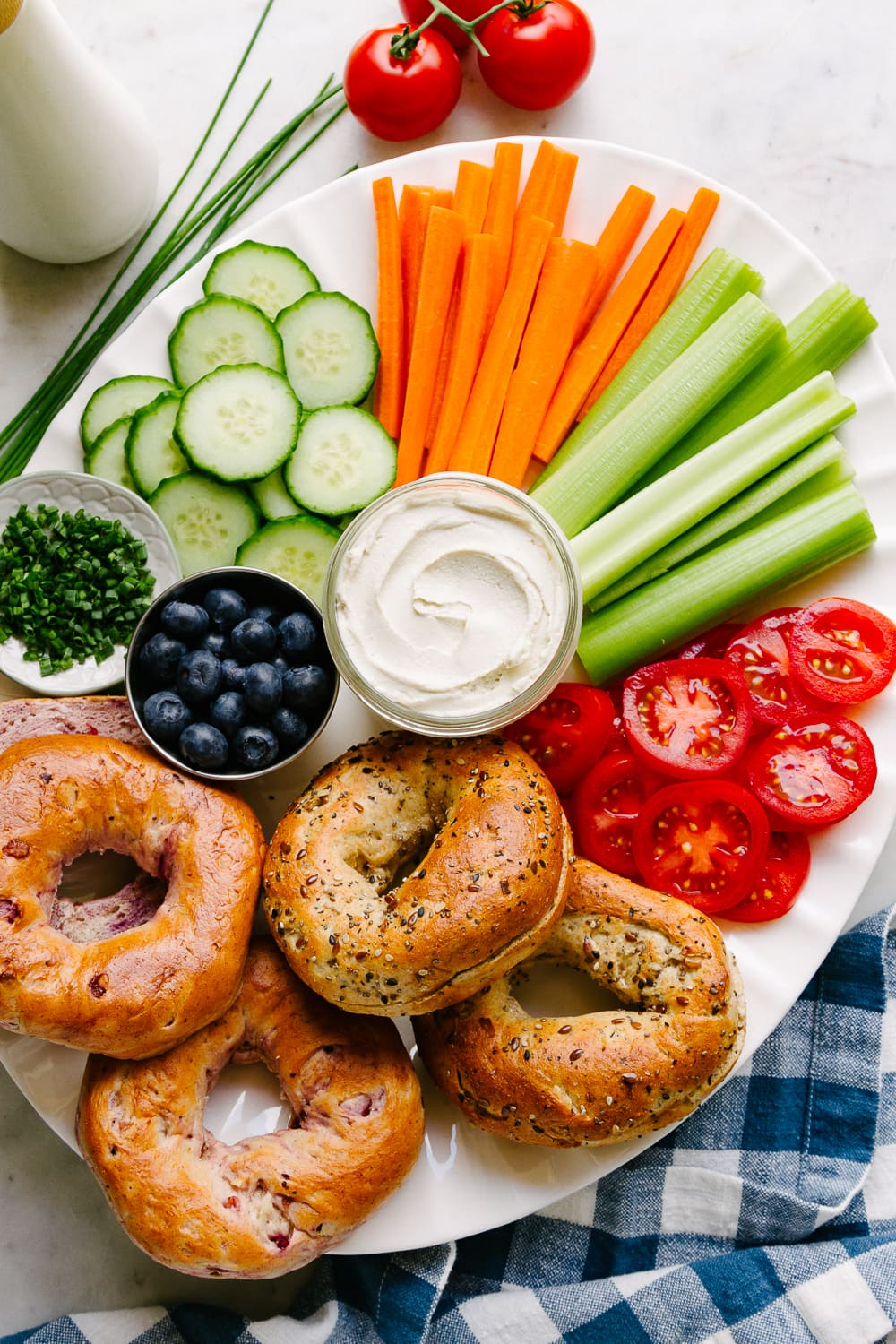 top down view of a vegan cream cheese and bagel platter with veggies and fruit.