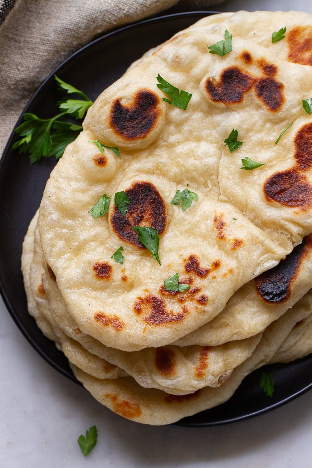 top down view of freshly made vegan naan bread stacked on a black plate.