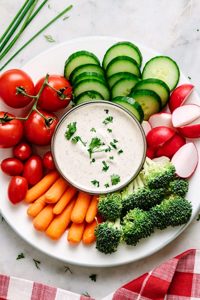top down view of a platter plate with fresh veggies and small bowl of easy vegan ranch dressing-dip in the center.