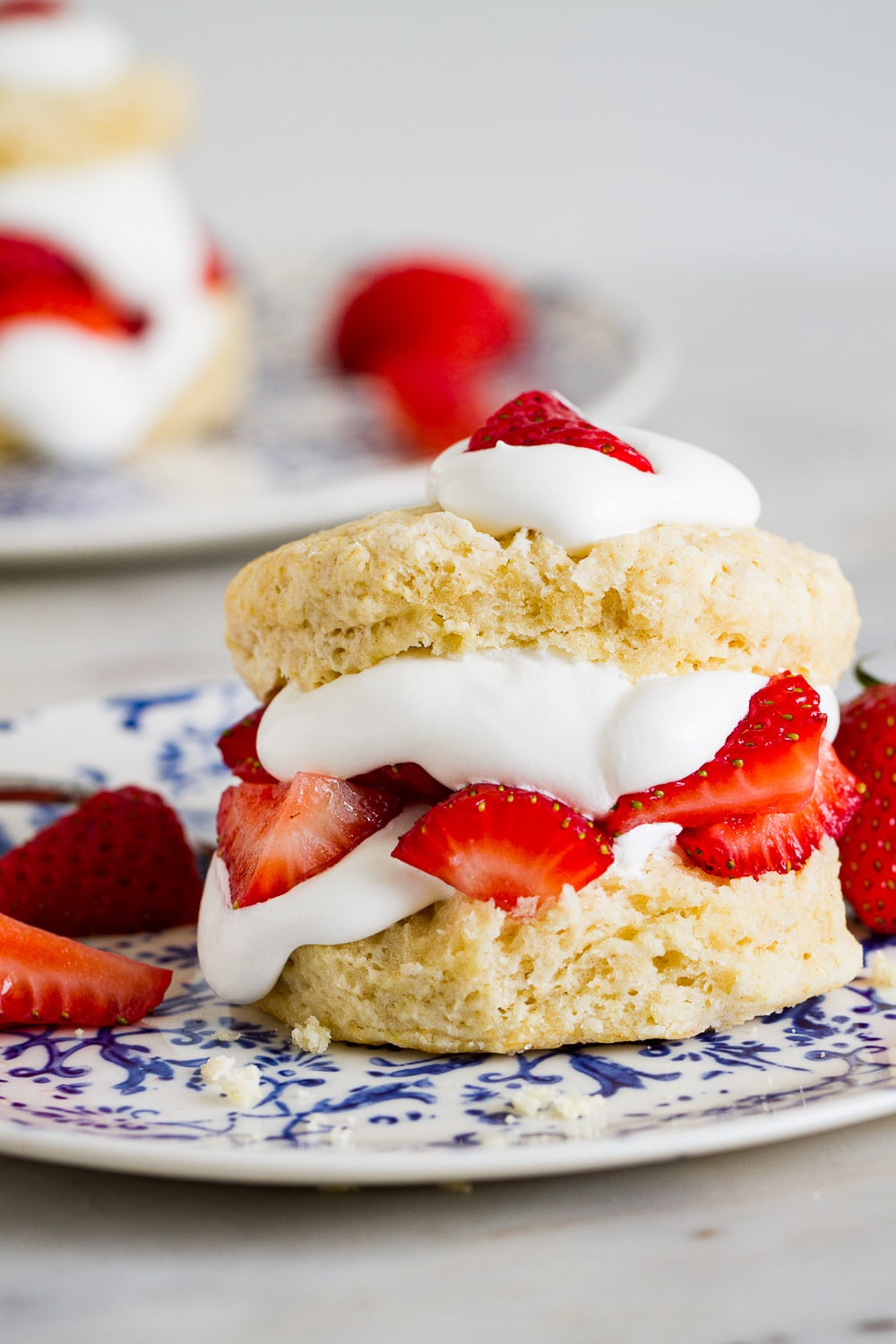 top down view of vegan strawberry shortcake on a blue and white plate with fork.