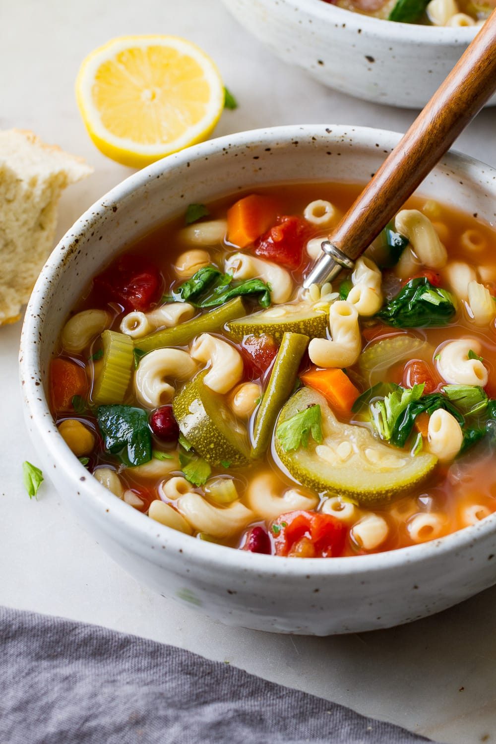 side angle view of healthy vegan minestrone soup in a bowl with wooden spoon.