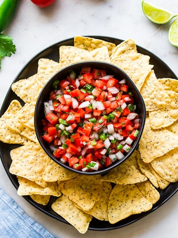 top down view of a bowl with fresh pico de gallo surrounded by tortilla chips.