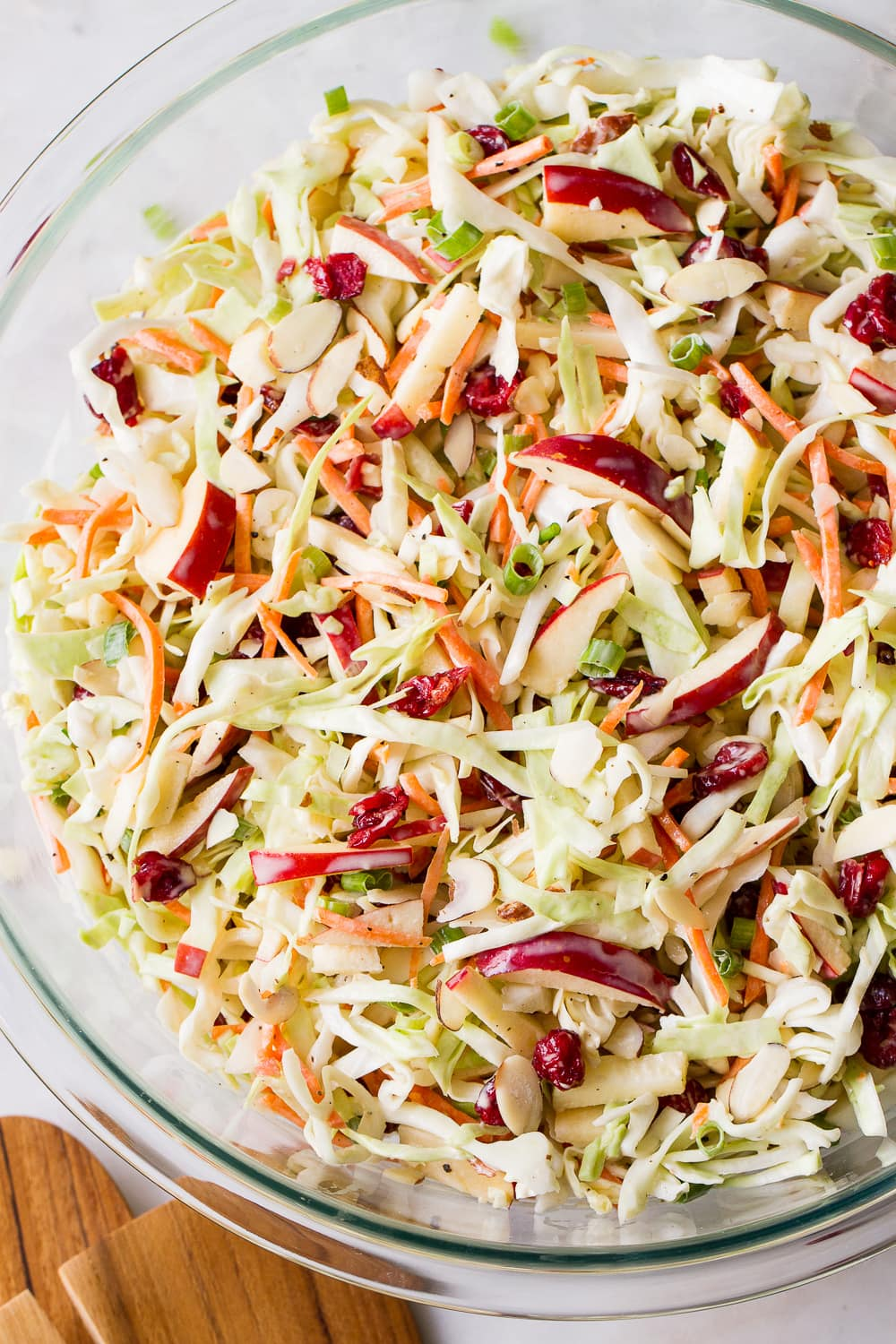 top down view of freshly mixed easy apple coleslaw in a glass bowl.