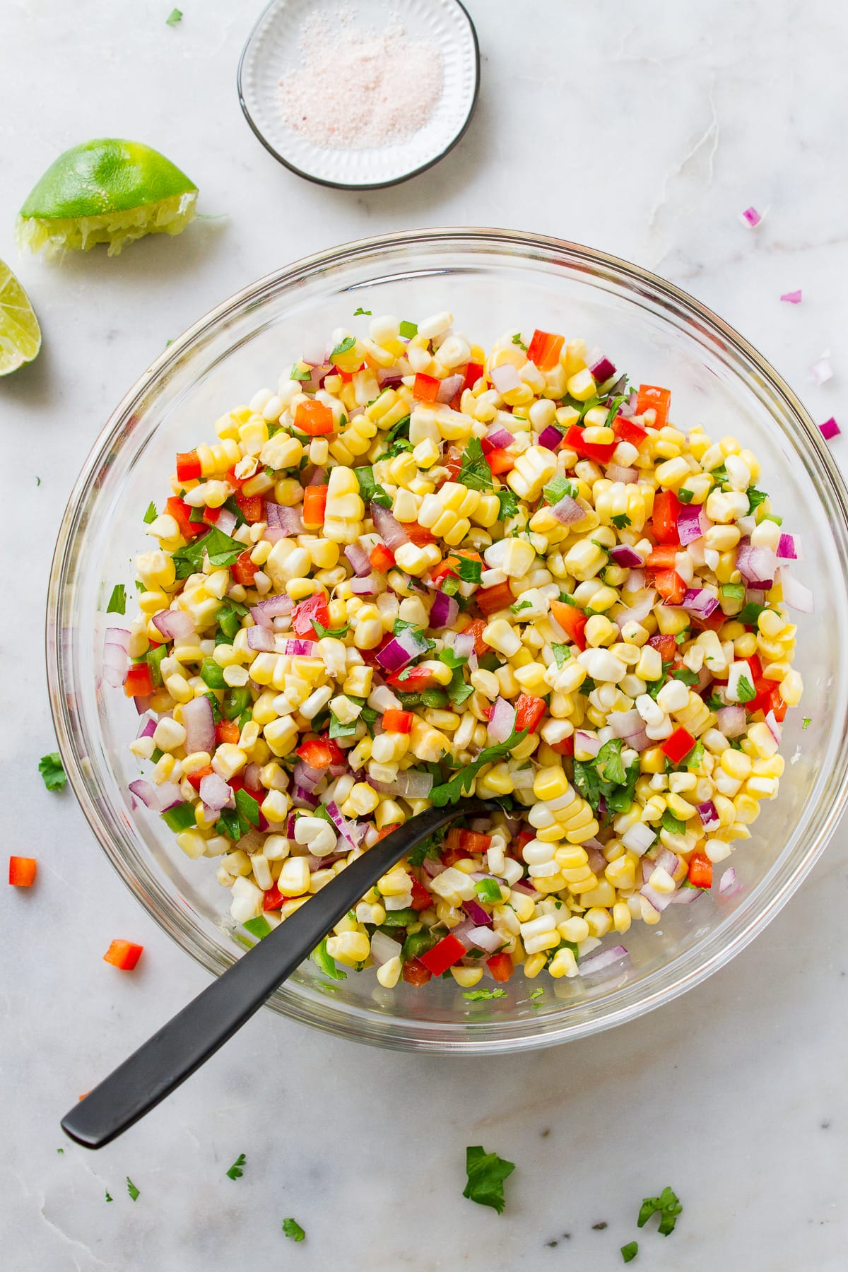 top down view of simple freshly made corn salsa in a glass mixing bowl.