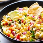 side angle view of simple fresh corn salsa in a black bowl.