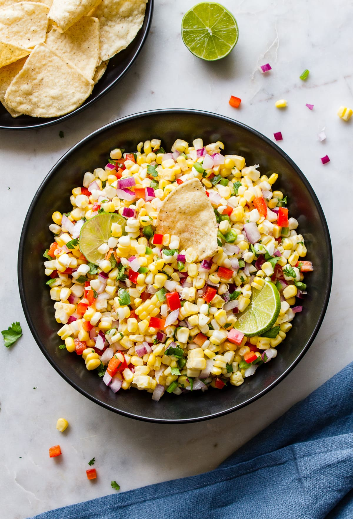 top down view of simple fresh corn salsa in a black bowl.