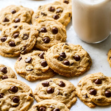 side angle view of a bunch of chocolate chip cookies laying on a marble slab with glass of almond milk nearby.