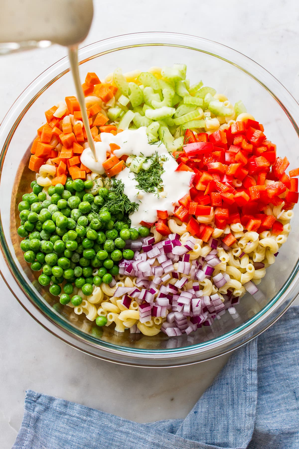 top down view of ingredients to make vegan macaroni salad in a glass bowl with creamy dressing being poured overtop.