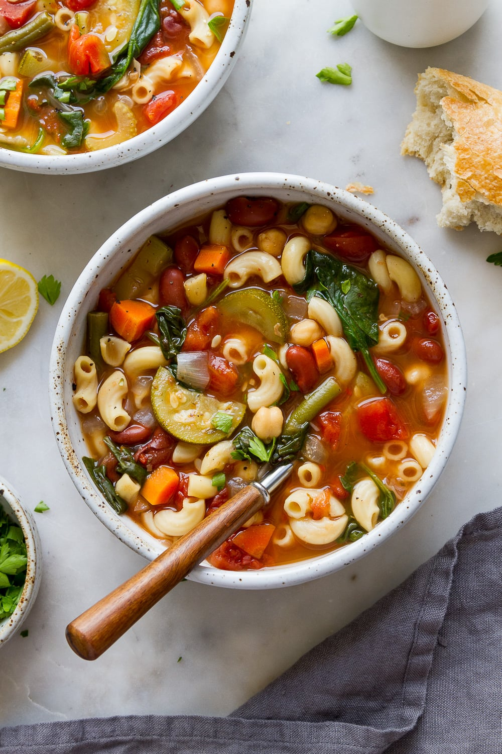 top down view of a bowl full of freshly made easy vegan minestrone with wooden spoon.