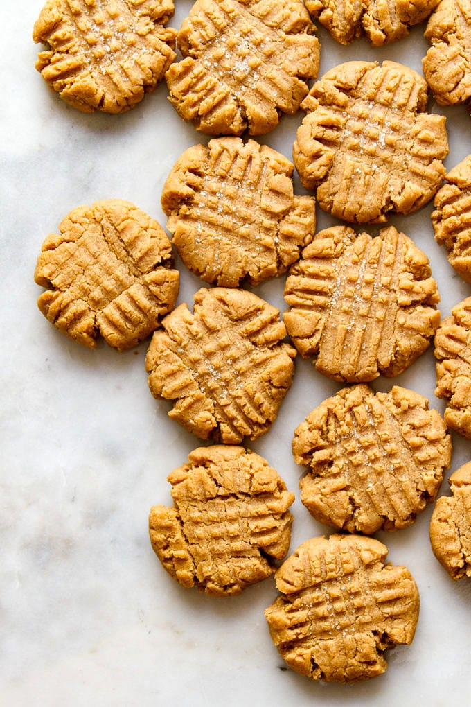 top down view of a cluster of vegan peanut butter cookies on a marble slab.