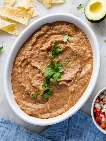 top down view of refried beans in a white serving bowl with chopped cilantro sprinkled overtop.
