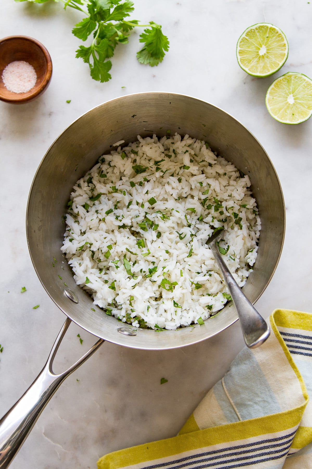 top down view of freshly made cilantro lime rice in a pan with fork.