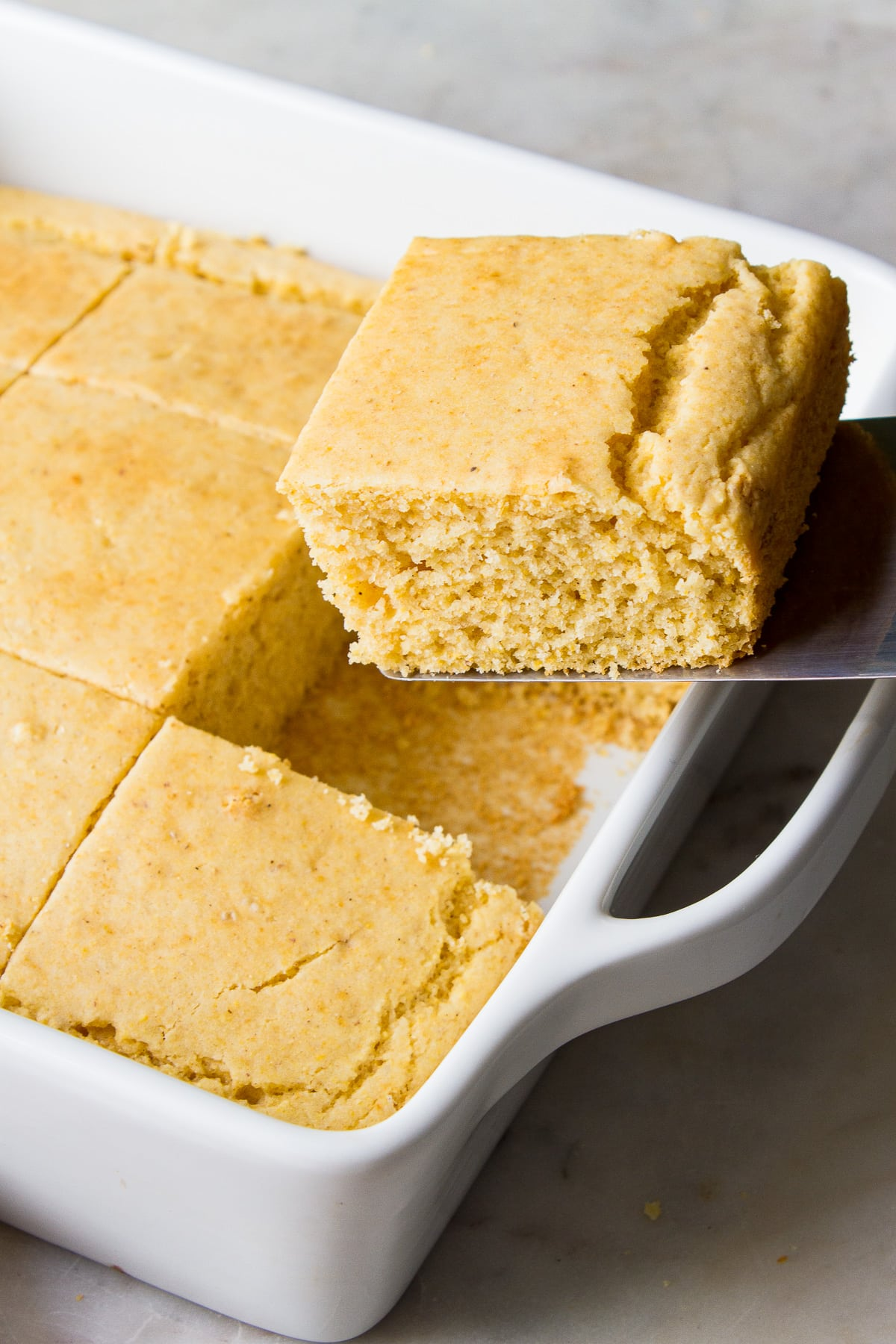 side angle view of cornbread being lifted from baking dish with spatula.