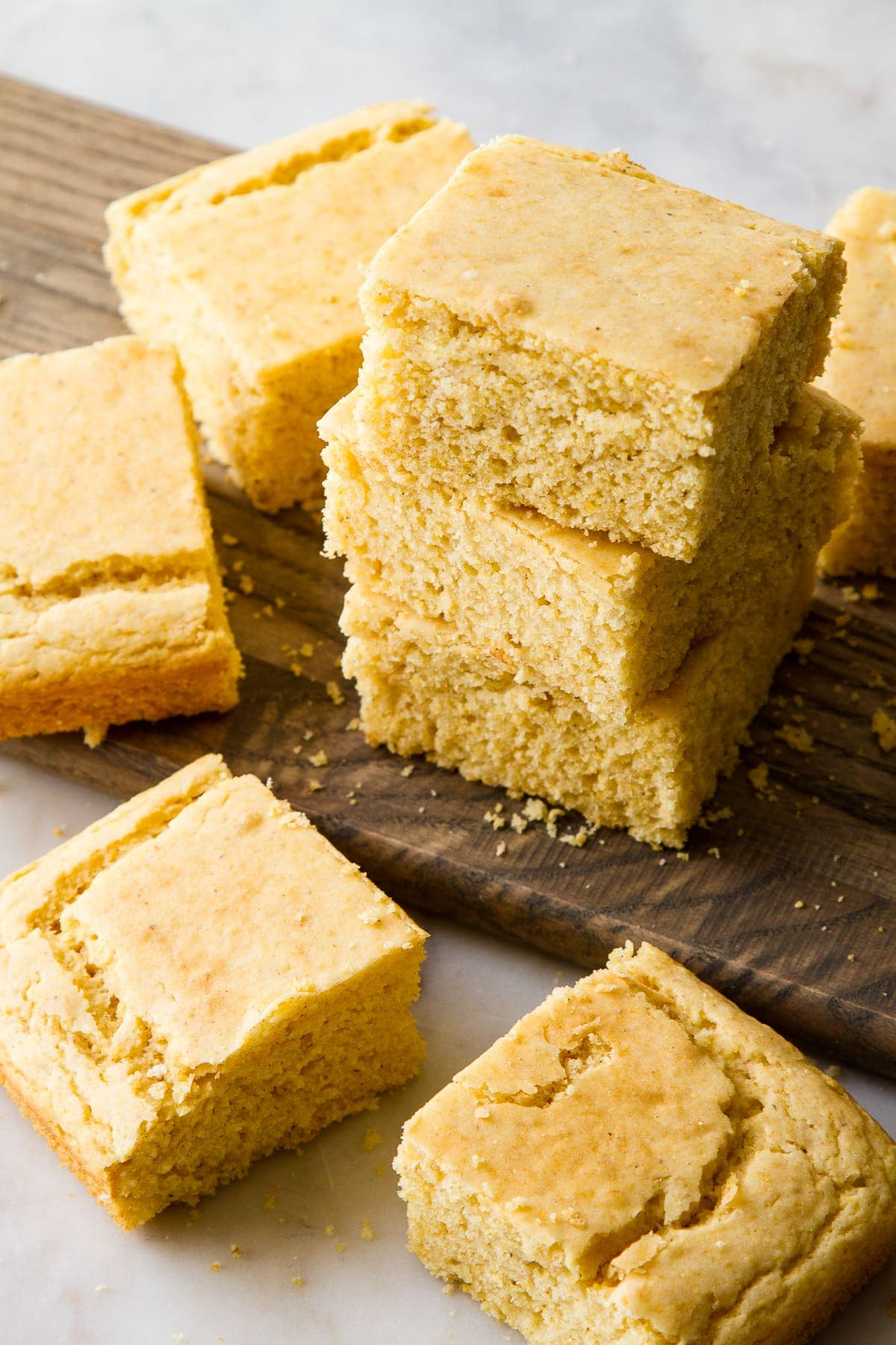 side angle view of slices of freshly made vegan cornbread on a wooden serving board.