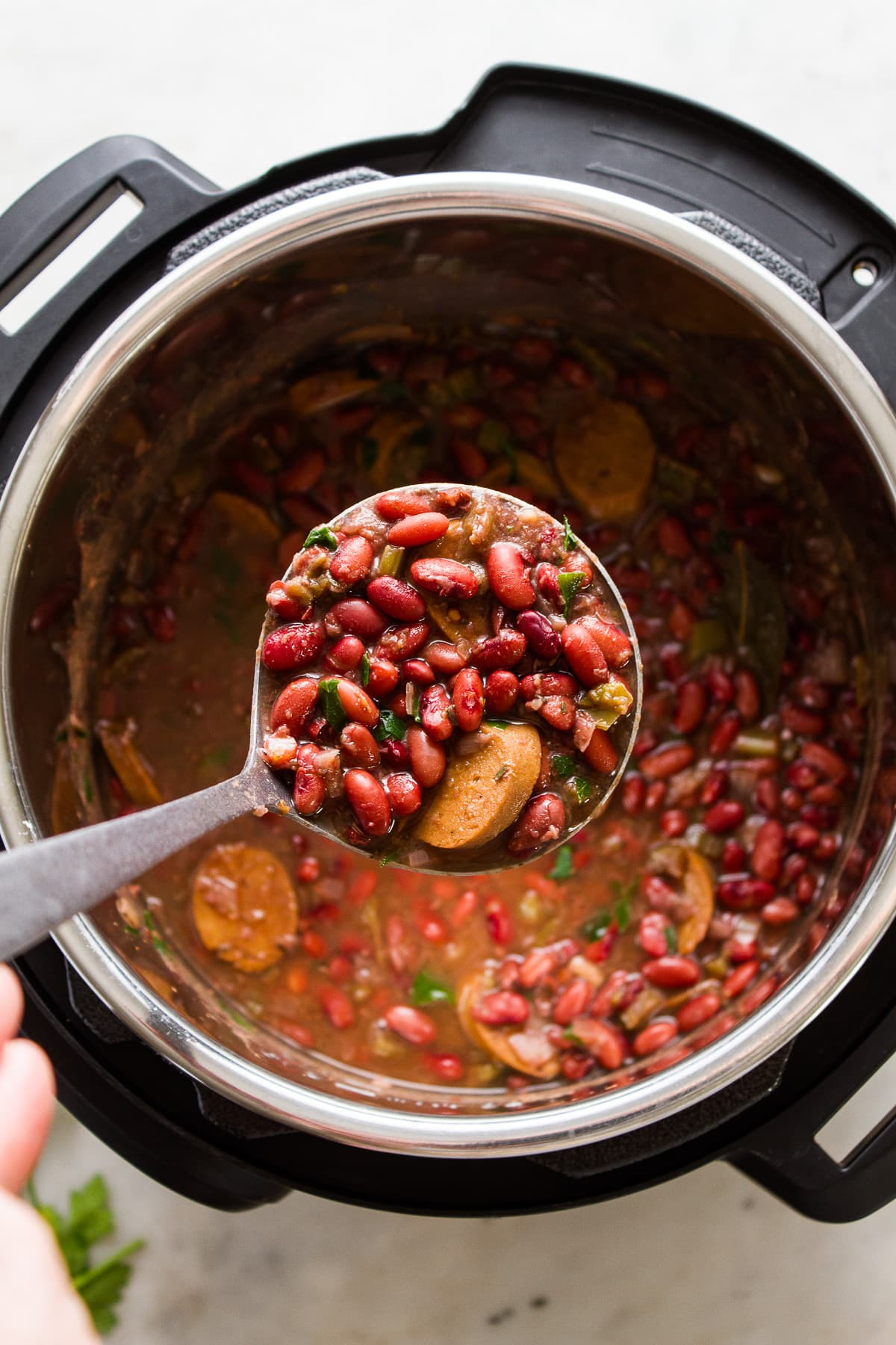 top down view of an instant pot with a ladle holding a ladle full of cajun style red beans.