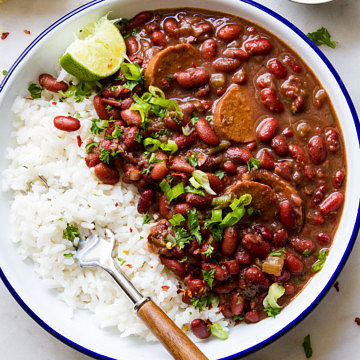 top down view of a white bowl with blue rim filled with a serving of vegan red beans and rice.