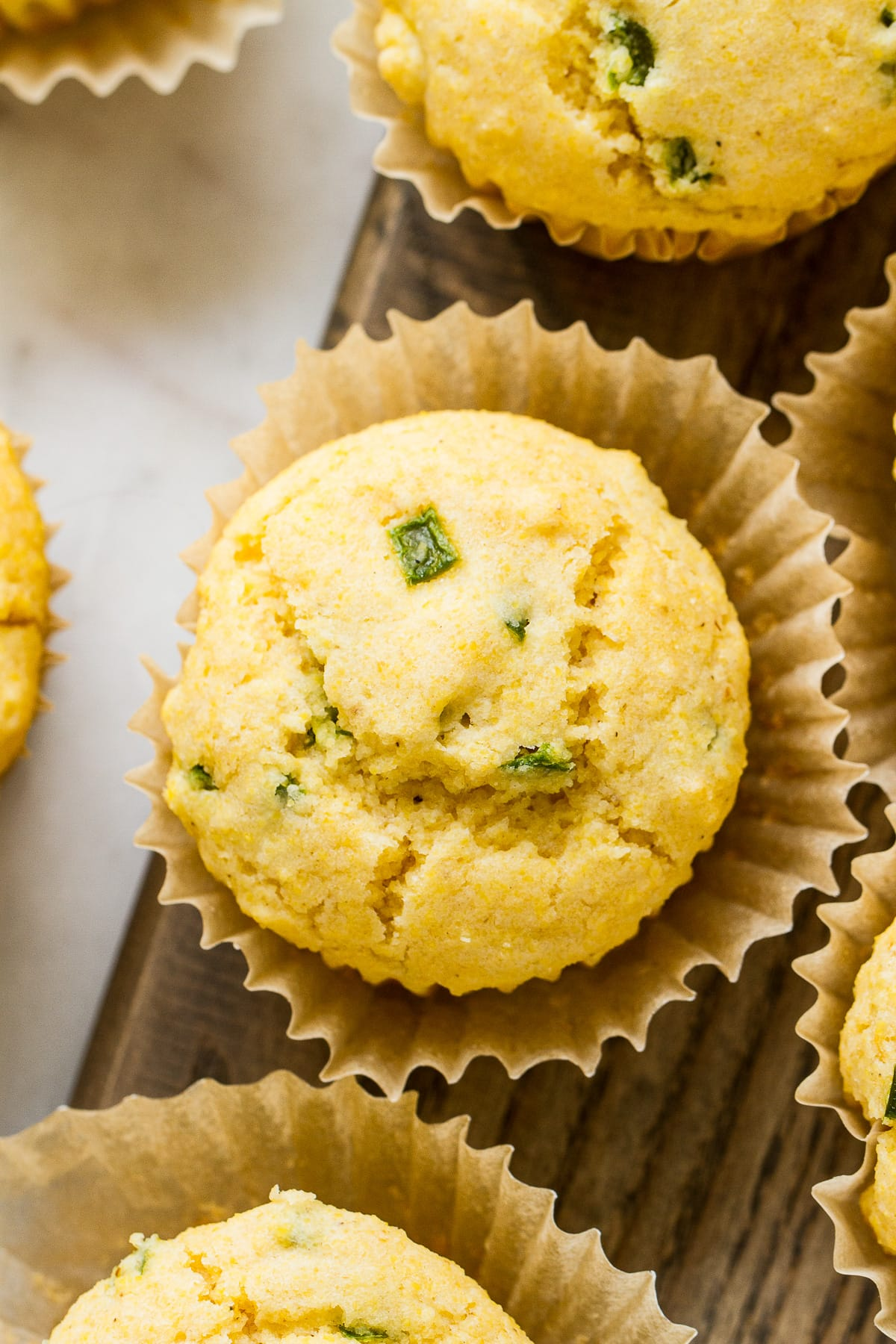 top down, up close, view of vegan corn muffins with jalapenos surrounded by other corn muffins.