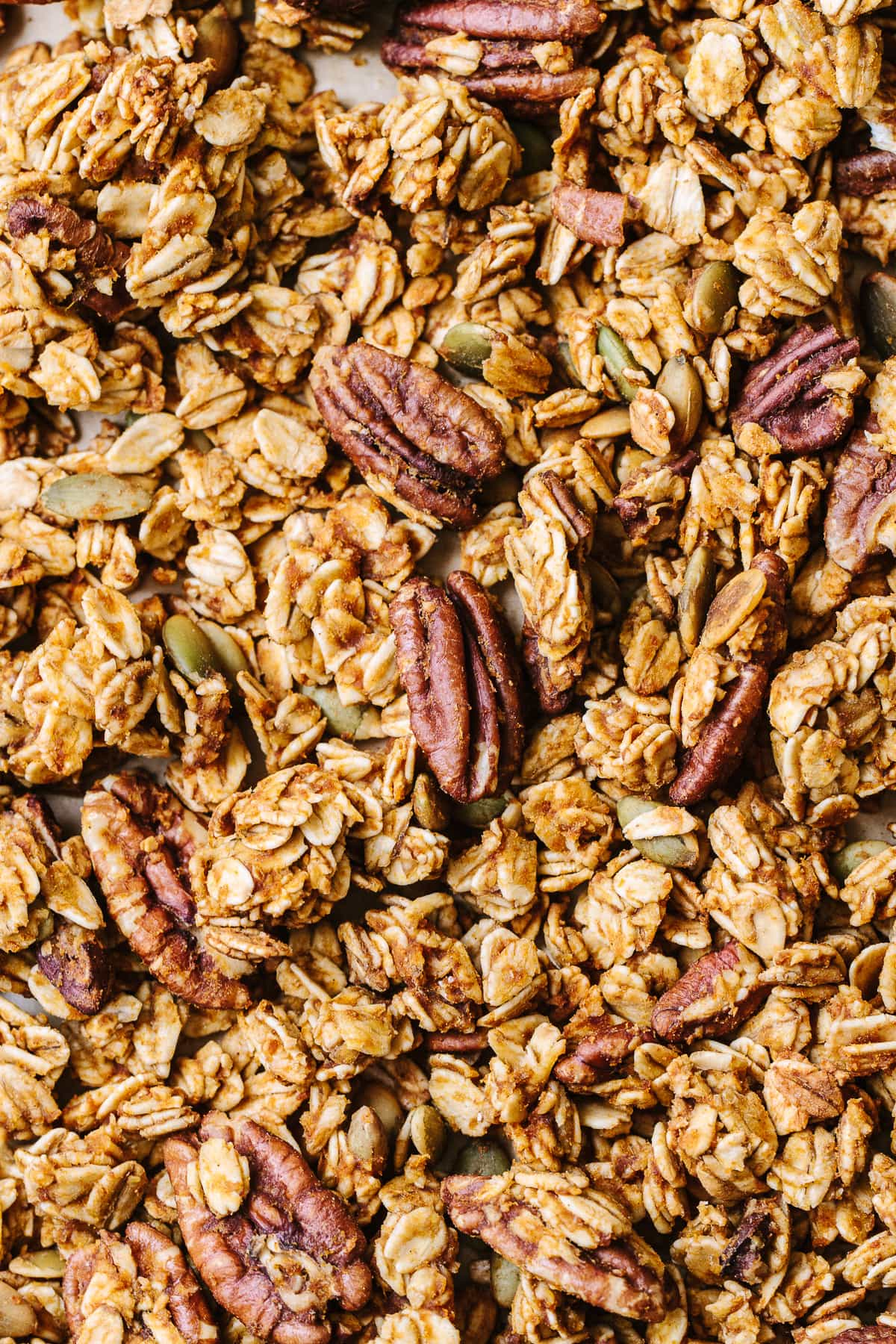 top down view of freshly made healthy pumpkin granola on a baking sheet.