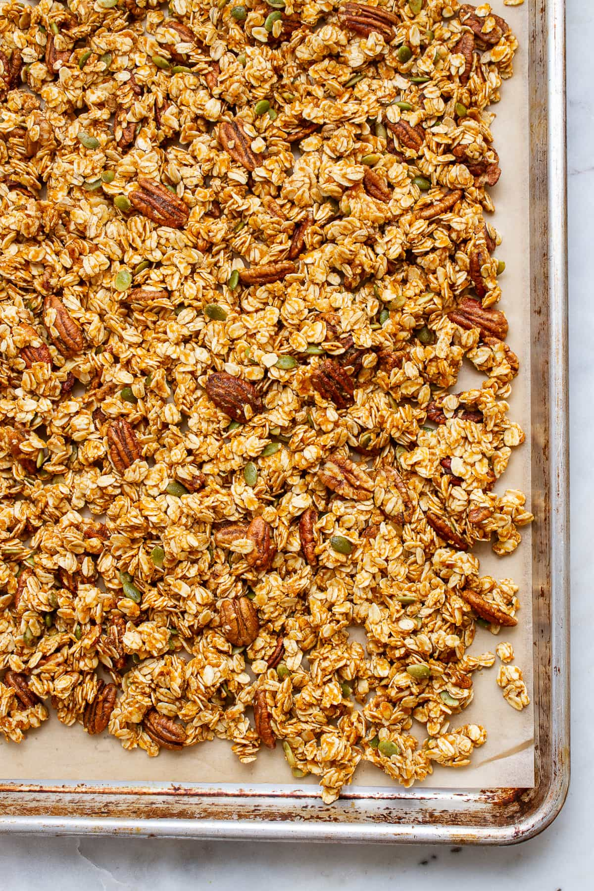 top down view of oil free pumpkin granola spread on a baking sheet before going into the oven to bake.