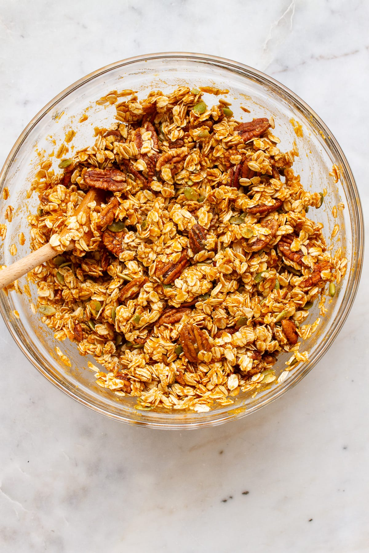 top down view of a bowl with all ingredients for pumpkin granola added and mixed.