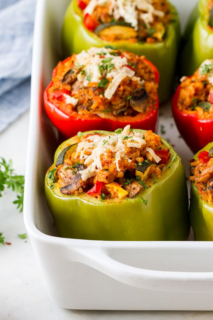 side angle view of vegan stuffed bell peppers freshly baked in a baking dish.