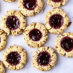 top down view of freshly made almond flour thumbprint cookies on a marble slab.