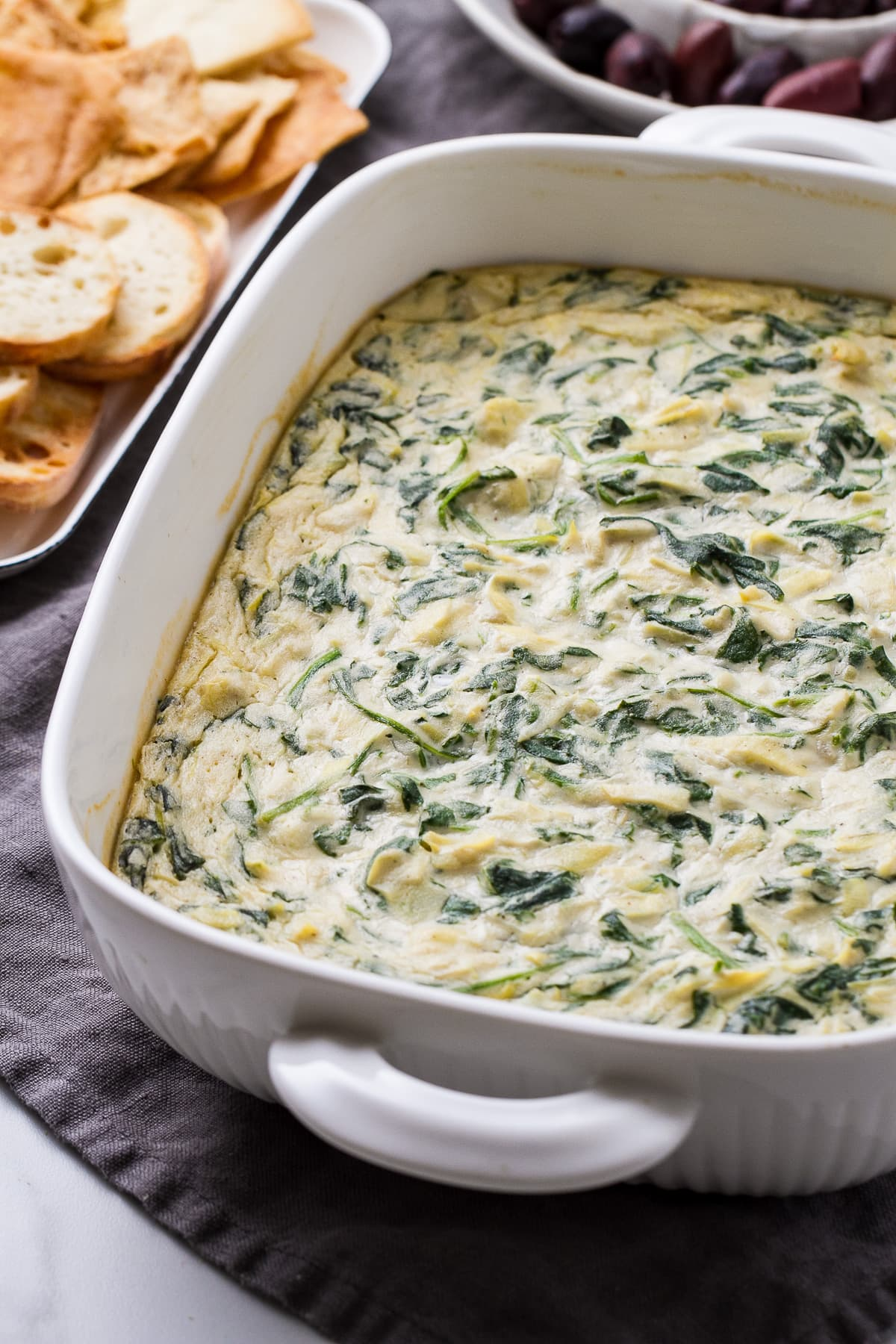 side angle view of prepared vegan spinach artichoke dip with items surrounded.