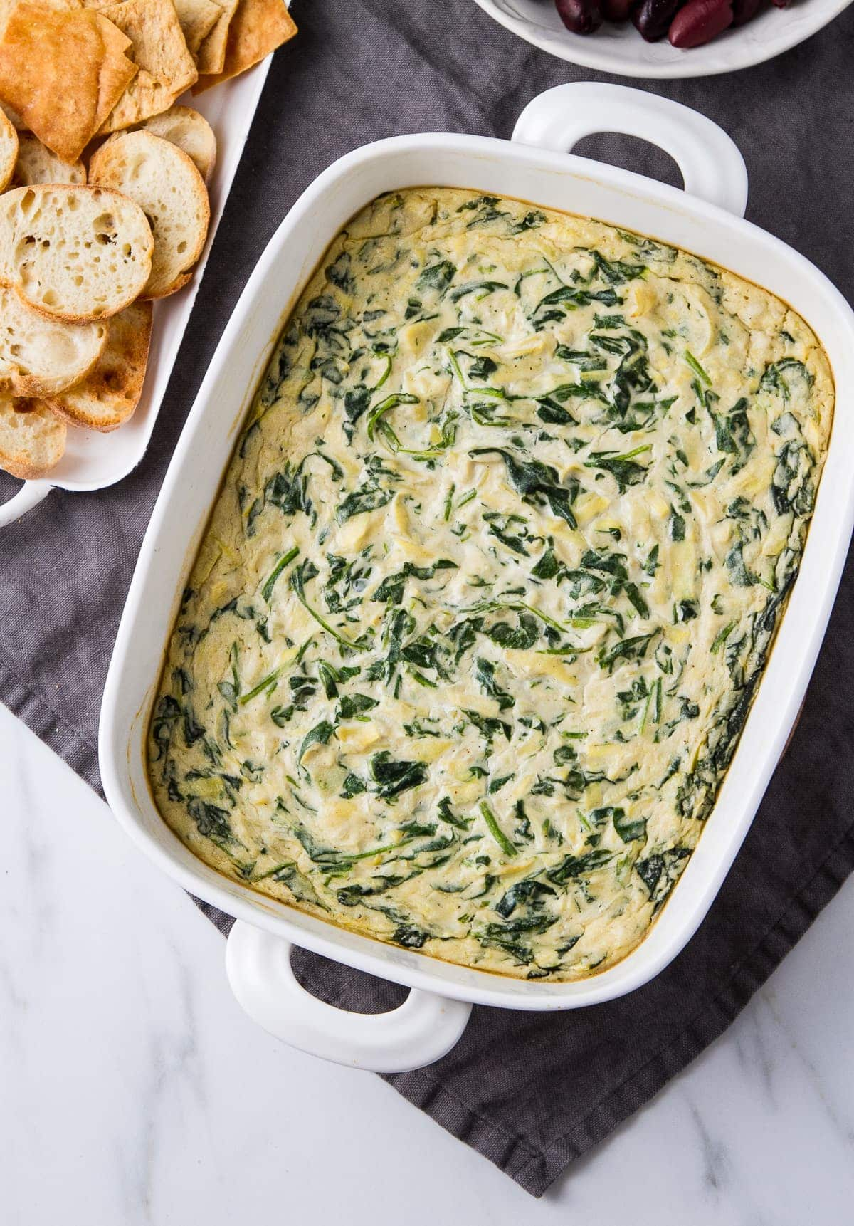 top down view of prepared vegan spinach artichoke dip with items surrounded.