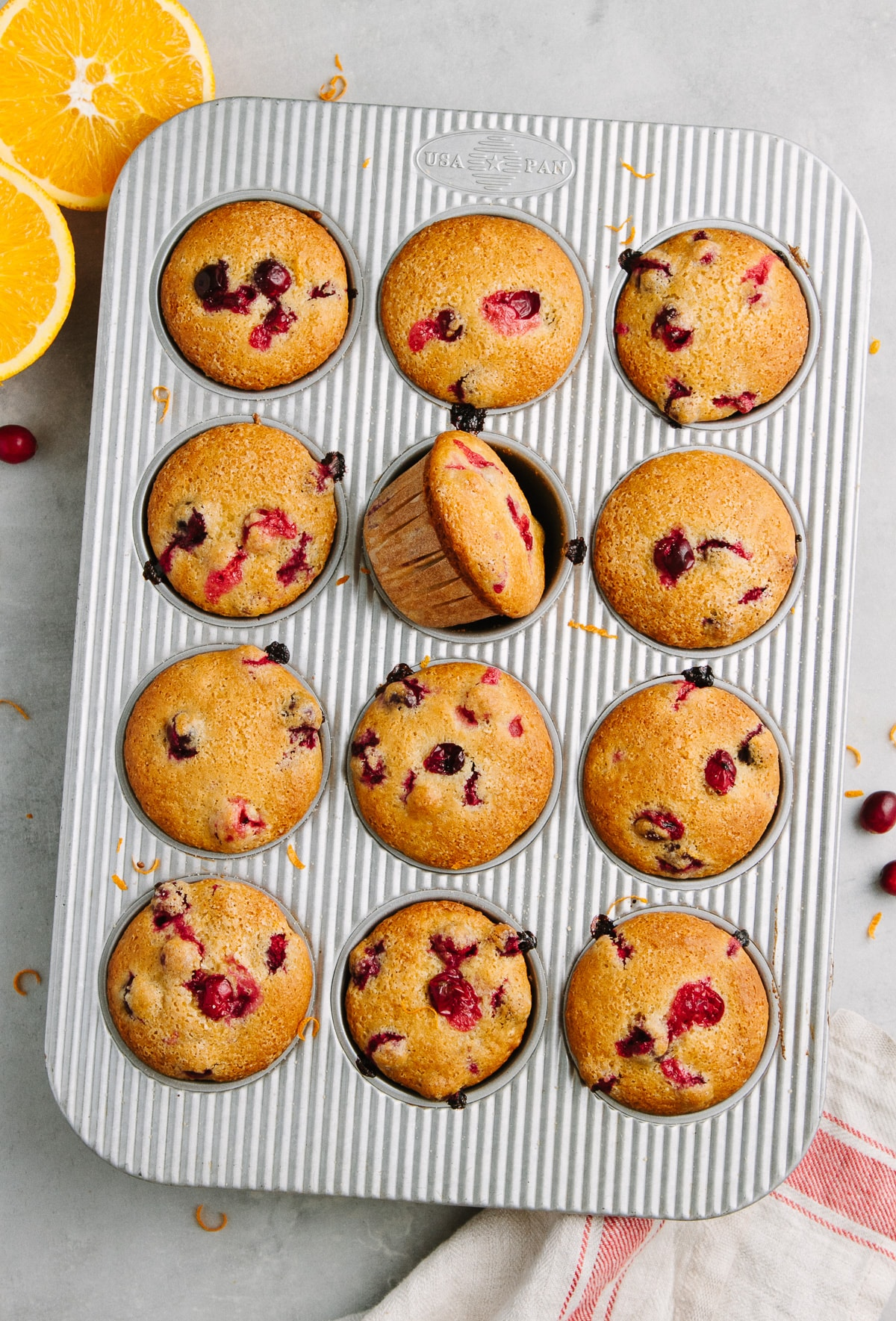 top down view of freshly made healthy vegan cranberry orange muffins in a muffin tin.