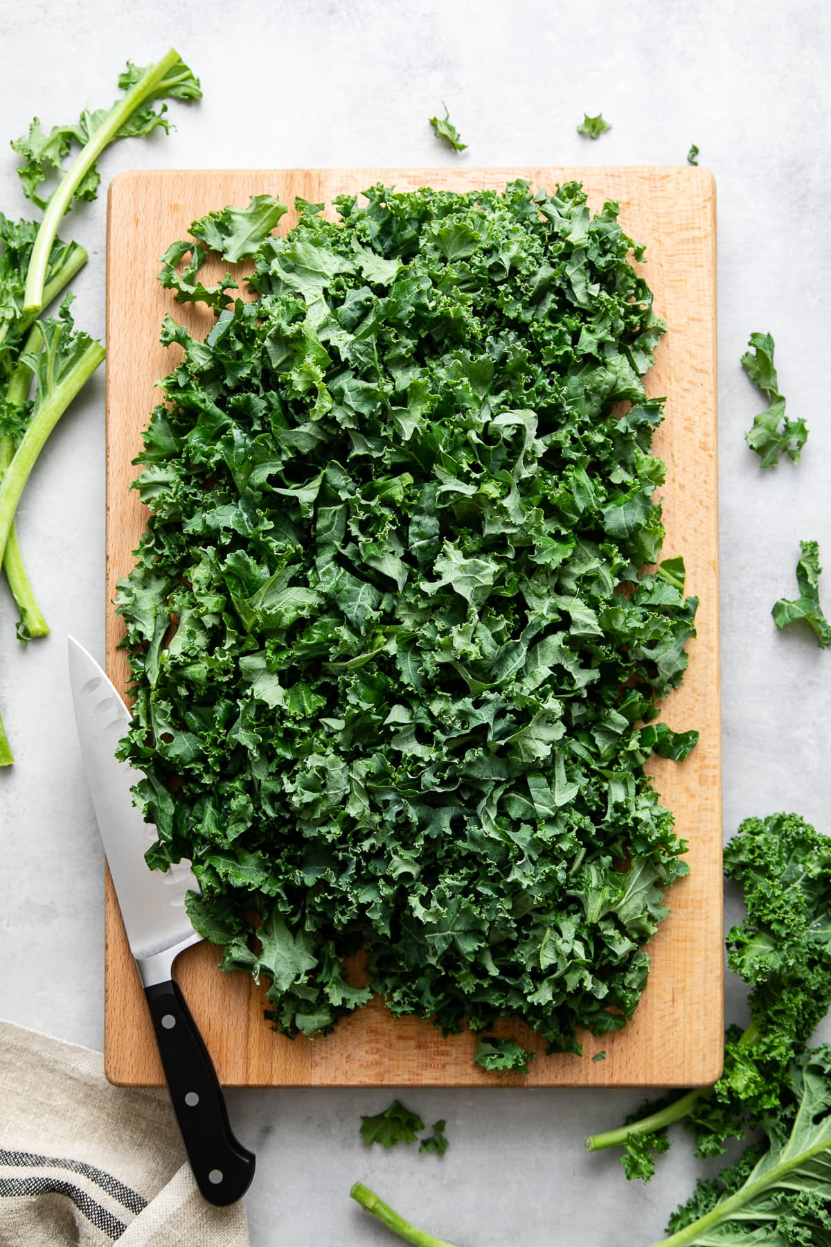 top down view of chopped kale on a cutting board with items surrounded.